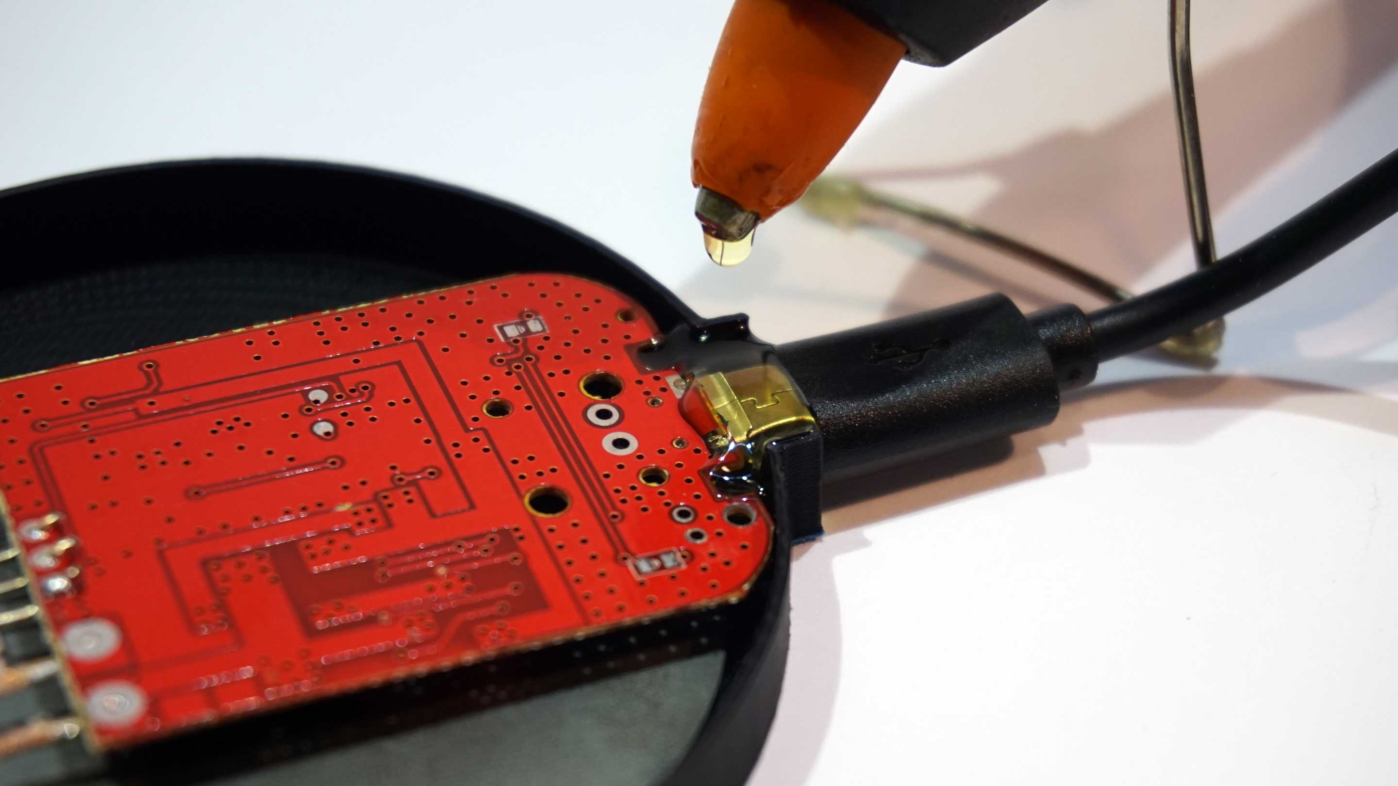 Don't be afraid of using too much glue. It is non-conductive, will not short anything out and will not damage the PCB .